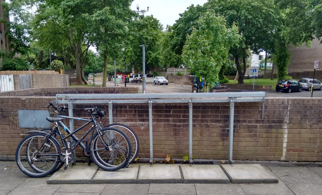 Bikes locked to a wheelie-bin rack